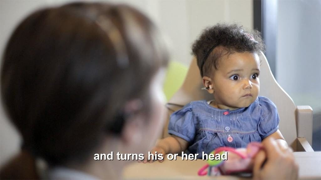 A scene from the training videos for the Eduplex Training Institute filmed by Zikedish, showing a little deaf girl responding to sound stimulus and turning her head.